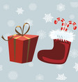 santa claus boots and red gift gray background vector image vector image