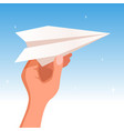hand holding a paper plane on the blue sky vector image