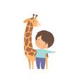cute boy with giraffe kid interacting with animal