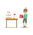 Boy Holding A Present Standing Next To Table With vector image vector image