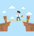 businessman walking on rope across cliff risk vector image