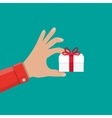 Hand holding white gift box with red bow vector image vector image