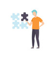 young man connecting puzzle elements together vector image
