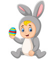 cartoon baboy wearing easter bunny costume hold vector image vector image