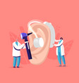 tiny male female doctors fitting deaf aid on huge vector image