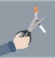Hand scissors cutting a cigarrette