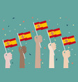 hands holding up spain flags vector image vector image