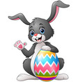 cartoon bunny waving hand with holding easter egg vector image vector image