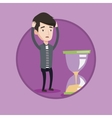 Desperate businessman looking at hourglass vector image