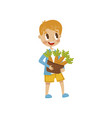 cute little boy holding basket full of carrots vector image