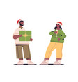 couple in santa claus hats having fun with gift vector image vector image