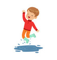 cute little boy playing on a puddle wearing rubber vector image vector image