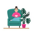 Cute woman in armchair with a cup coffee